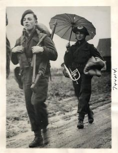 1944- Canadian medical corpsman forms an odd picture with his bugle dangling from his belt, and an umbrella to protect him from Holland's wet weather, as he follows fellow soldiers through a Dutch village near the Canadian Front.