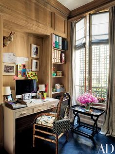 Paneled in cerused oak, the study includes a vintage Jean-Michel Frank desk and an heirloom bamboo chair; the handbag is by Dior | archdigest.com