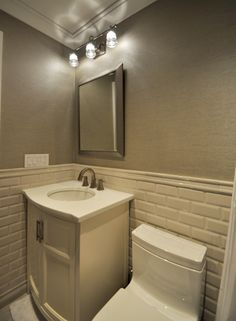 Bevel Edged Subway Tile with Vinyl Wallpaper, Toto Toilet Bowl, Grohe Fixtures and White Glass Vanity Top.