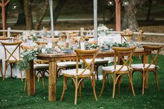 Modern, rustic chic wedding reception decor - rustic wood farm tables, x-back chairs and romantic flower garland table runners {Lovers of Love Photography}