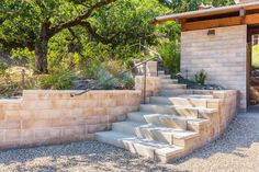 """The  rammed earth Watershed Block  walls in this sustainable private residence by Arkin Tilt architects curve ever-so-slightly along the entry drive and up to the compound. The block walls serve to retain the hillside. The six-inch high blocks, sixteen inches in length, provide an optimum """"rise over run"""" for a gradual ascent. The retaining wall caps are cast using the same formula as the blocks themselves.  Image © Ed Caldwell"""