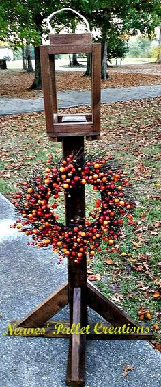 """RECYCLED WOOD PALLETS: This is a Porch Wreath Holder with a Lantern top and double hook underneath. You could put an electric light or candle in the lantern part, or add some Christmas garland or Fall garland to dress the lantern up.  The Wreath Holder is 5 feet tall and has a 32"""" wide base. The lantern on top is 16"""" high x 8.5"""" wide x 9"""" deep. We are selling this one for $50. Item#806"""