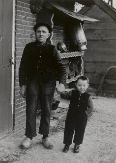 Hendrik Veyer Senior en zijn kleinzoon Hendrik Veyer Junior 1952 Hendrik Junior is gekleed in de overgangsfase van streekdracht naar burgerdracht. Hij draagt nog wel een keelknoop en traditionele klepbroek, maar deze in combinatie met een gebreide trui i.p.v. de traditionele hemdrok. Op de achtergrond een houten melkbussenrek. #Overijssel #Staphorst