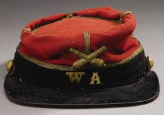 """Confederate Louisiana """"Washington Artillery"""" Officer's Artillery Kepi. 6.5"""" wide x 9"""" long, high red wool crown, dark blue wool hatband, single line of gold trim, stamped brass crossed cannon insignia, stamped brass """"W A"""" on front of hatband, patent leather visor and remnants of chinstrap secured by two 16mm eagle staff buttons.The brave men of the Washington Artillery fought gallantly in every battle during four years' service with Lee's Army of Northern Virginia."""