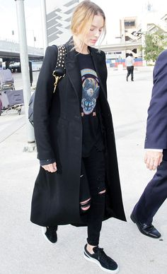Margot Robbie wore a chic but comfy ensemble of a black graphic T-shirt, ripped jeans, a long line coat, designer handbag, and a pair of Puma's classic suede trainers to the airport.