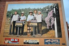 THE PEOPLE BEHIND THE LABEL Artist: Chuck Caplinger, Twenty-nine Palms, Ca (2001)  The Emperor Grapes was once of great economic importance to Exeter. This mural also illustrates the prominence of two local families .