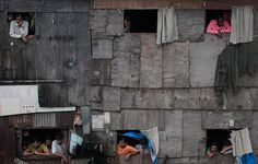 Mumbai, India: People watch a rally outside a shanty town