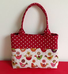 Red and beige handbag featuring birds