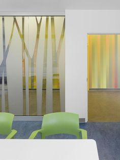 A meeting room for midwives is screened off by an abstract pattern of a stand of birch trees cut in frosted film. Photo: A-Frame/Ben Rahn
