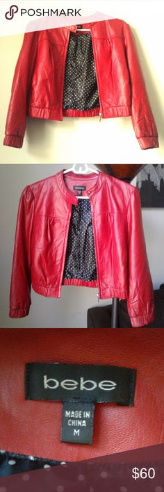 Just reduced bebe RED HOT MOTO JACKET! Stunning red genuine leather bebe moto jacket. Cute polka dotted lining inside! In good condition. There is a small crack/rip on the left arm, pictured above, and also some loose stitching on the lining (also pictured above). Sleeve is a three-quarter length. Super edgy and cute at the same time! bebe Jackets & Coats