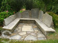 All this stone bench needs is a stone fire pit and it would be perfect seating to an outdoor kitchen.