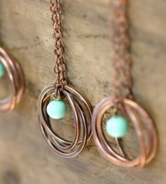 """Organic, causal and modern and all in one necklace! Three oxidized copper rings that are linked together and hang from a 24"""" copper chain.    Each ring is soldered together so there is a little bit of silver solder at each ring joint.    It is finished with a small vintage Japanesse baby blue glass bead."""