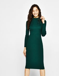 """This gorgeous <a href=""""https://www.bershka.com/gb/woman/clothing/dresses/ribbed-dress-with-button-neck-c1010193213p101097570.html?colorId=594"""" target=""""_blank"""" data-skimlinks-tracking='4676420'>ribbed jumper dress</a> in emerald green."""