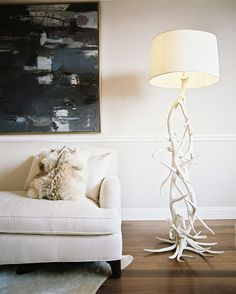Living Room - A floor lamp made of antlers beside a white couch