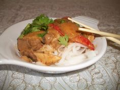 Thai dish: mango curry with chicken and rice noodles. Served with cilantro for décor.