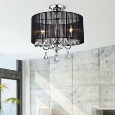 This semi flush-mount crystal chandelier adds refined style to most any living space. Ideal for a dining room or kitchen, this beautiful chandelier features a chrome frame with clear crystal accents. The elegant black shade makes this chandelier unique.