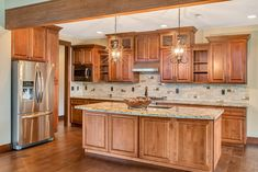 Stunning craftsman style kitchen. Alder cabinets with raised panel doors and drawers, slab granite counters with a curved edge for an elegant yet functional island. Photo Bill Johnson Photography