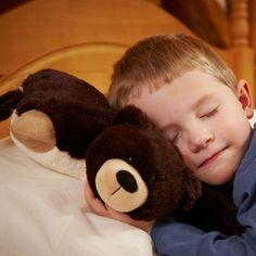 Criança dormindo com almofada pelúcia.