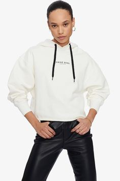 A luxe hooded sweatshirt constructed from soft 100% cotton. Cropped, boxy silhouette, raw hemline, and understated ANINE BING graphic with black leather pants #athleisure #fall2020