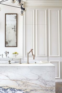 A marble block kitchen island might sound like a bold design choice, but blogger Jacquelyn, of Jacquelyn Clark, shows you how to make it work in the elegant interior design post. Custom cabinets and an all-white color palette give this elegant kitchen a sophisticated look.