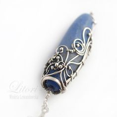 Pendant on a longitudinal and two faces. One gentle and soothing like the ocean waves. Second aggressive and restless. Silver casing is made ​​from scratch by hand labor-intensive wire-wrapping technique. Closes in a large, blue agate fire