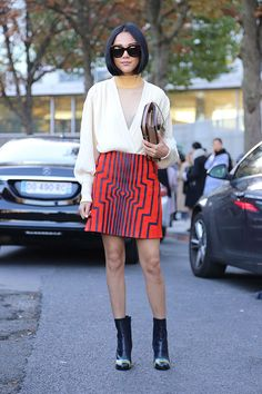 Yoyo Cao struts the streets of Paris in her 60's inspired style. This fashion maven paired a sheer layered turtleneck with a mod skirt and black booties accented with stripes for a chic look.