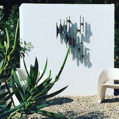 Serge Castella garden with brutalist sculpture and Ron Arad chair