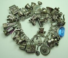 1970s English silver charm bracelet with 25 charms including 8 opening, 8 moving and 3 crystal, 105g - 268 gbp