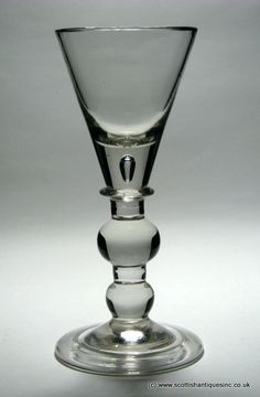 One of only three known examples, this is a very rare large heavy baluster wine glass goblet c 1710.  It has an unusual narrow conical bowl with solid base with an air tear. The stem has an angular collar above a large ball knop and basal knop. The glass stands on a conical folded foot.  http://scottishantiques.com/georgian-wine-glasses/baluster-stems/very-rare-goblet#.ViP1PcZ2lTN