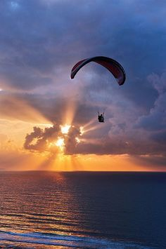 oceanflower2015:  paragliding at sunset on sea with sun beams by Mimadeo