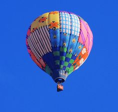 In a rainbow of colors, a patchwork quilt style balloon, was flying high in the blue skies of Colorado Springs, CO. The morning clouds cleared just in time.