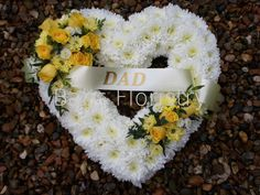 Open heart tribute based with white Chrysanthemums. Two sprays of yellow blooms finished off with a sash and name.