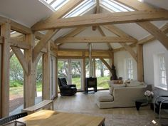 Lovely, simple living space with exposed oak frame in curved annex building by Roderick James Architects