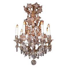 Louis XV Style Rock Crystal Chandelier  France  Early 20th century  Louis XV style eight arm brass and rock crystal, cage    chandelier in the manner of Maison Bagues, with floral     and foliate pendants, finished with rock crystal ball.