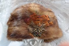 Beautiful vintage mink fur hat. This pillbox hat made out of mink fur is almost new, decorated with a vintage stone and feathers. The mink hat is in great condition. The texture is soft, shiny and very aristocratic looking. I can imagine the previous Hungarian owner, wore this hat with lot of care and combined with A class coat and boots. The vintage fur hat can be perfect gift to someone that you love and has everything and will be glad to have a extra hat in winter.  The headband measures…