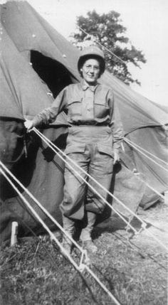 A 1st Lt. of the 203d General Hospital identified as simply « Mac », is pictured standing in the doorway of an M1934 Pyramidal Tent in Normandy ~