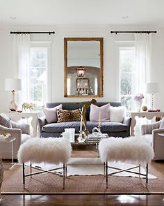 White curtain, dark rods, gray sofa, leopard pillow, gold accents, wooly stools