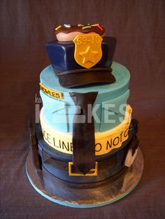 Police Officer Retirement Cake All 3 cake tiers iced in buttercream. Cop hat is covered in Marshmallow Fondant (MMF) MMF decorations