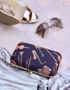 Showcase your love of music through this statement clutch. The orange/peach hued musical instruments set against the dark aubergine is perfect for a day or night look. Retro Fabric, Night Looks, Ramadan, Musical Instruments, Hue, The Darkest, Musicals, Peach, Summer
