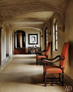 serene taupe hall with orange accented chairs ~ Axel Vervoordt design