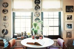 modern breakfast nook--tulip table, fornasetti plates, white roman shades