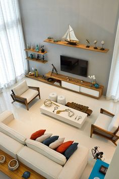 Floating wooden shelves in the living room with nautical themed decoration  h...