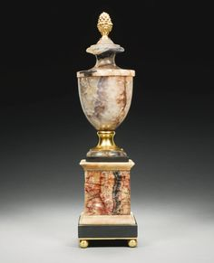 A George III fluorspa and blue john vase circa 1800 the urn with a brass acorn finial, on a brass socle, possibly later, on a white marble and blue john plinth and brass ball feet 40cm. high, 9.5cm. wide; 1ft. 3½in., 3¾in.