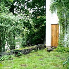 Aallon kotitalon puutarha aukeaa etelään. Eteläjulkisivu on muutenkin kiinnostavin kaikista: kun sitä katsoo kauempaa puutarhasta käsin syntyy erilaisten julkisivumateriaalien ja massojen sommittelun ansiosta vaikutelma kolmitasoisesta rakennuksesta vaikka katselemmekin kahta kerrosta. Puutarhan hedelmäpuut  liuskekivipolut ja villiviinit pehmentävät tarkoituksella rakennusta ja sen ympäristöä. Tontin rajaamiseen Aalto piirsi  heinäseipäistä ja betonipilareista kootun aidan. #alvaraalto…
