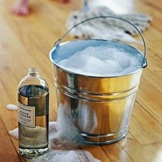 Wash your hardwood or pre-finished floors the old-fashioned way. Add a 1/2 cup vinegar to 1 gallon of hot water and mop or scrub as usual (make sure to barely wet your mop or cloth). Dry the floor completely with a towel afterward -- standing water is the enemy! Don't try this technique on waxed floors because it will strip off the wax finish. To lessen the smell of vinegar, add a drop or two of essential oil to your mix. Lemon- or lavender-scented oils are excellent options.
