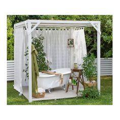 Romantiskt trädgårdsrum under en luftig baldakin.