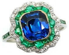 Art Deco sapphire, diamond, and emerald ring, circa 1915. A cushion-cut sapphire glows within a shaped cushion double border of emeralds and diamonds, and is further embellished by emerald line shoulders. Via Diamonds in the Library.
