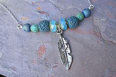 Blue druzy and dark teal lava stone with feather charm silver aromatherapy necklace, essential oil diffuser necklace. Silver essential oil diffuser necklace is on a sterling silver plated chain. Necklace can be made in 16 (choker length), 18 or 20 long, but adjustments to length can be