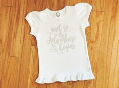 """This listing is for a girl's """"And So the Adventure Begins"""" graphic t-shirt. This beautiful children's top features a motivational quote in a handwritten font that is sure to provide inspiration for your little one. This tee shirt makes a lovely gift or a customized addition to your child's everyday wardrobe. Perfect for a traveling on a vacation or everyday adventures! Check it out here: https://www.etsy.com/heartfeltsy/listing/521779134"""