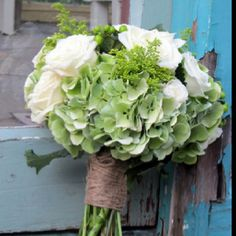 Bouquet by LovelyGirls Events Green Hydrangea, white roses, white ranunculus, and hypericum berries.